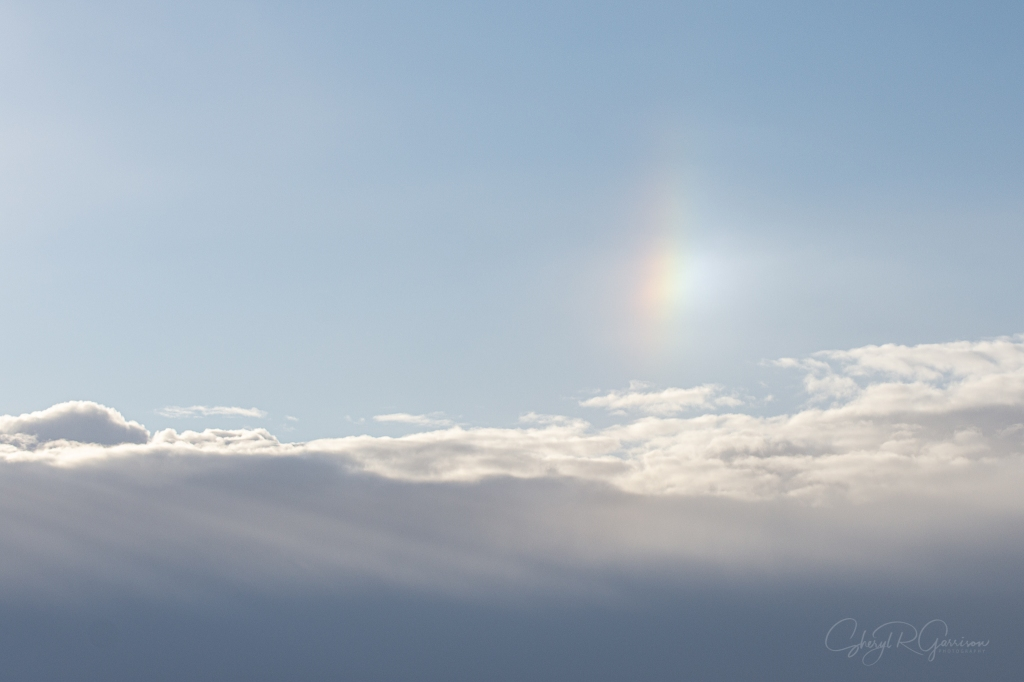 sundog over clouds with crepuscular rays
